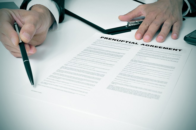 engaged couple sign prenup agreement