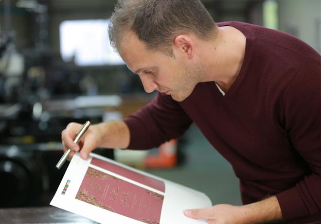 Giant Invitations graphic designer checking printed artwork