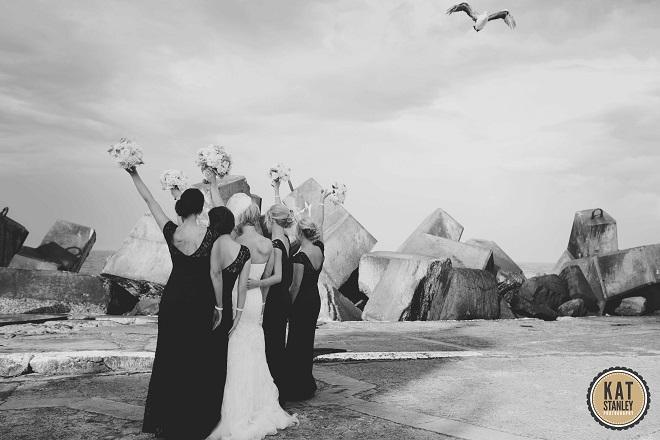 bridesmaids in black dresses celebrating with bride