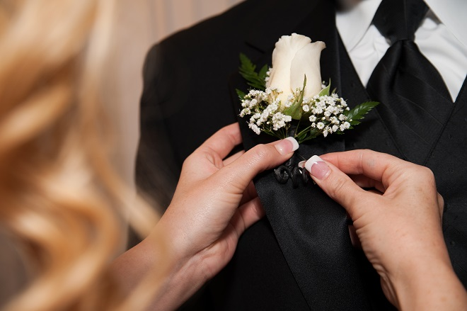 Groom adding a wedding boutonniere to his wedding suit