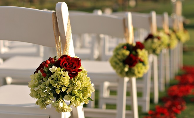 Decorating wedding ceremony chairs with flowers