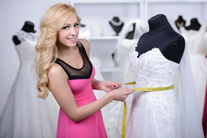 shop assistant taking measurements of wedding dress styles