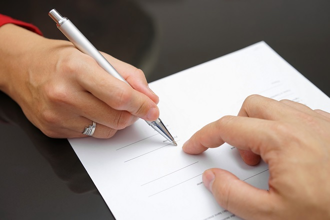 bride to be signing prenuptial agreement