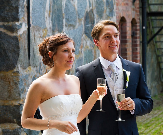 bride and groom looking at wedding guests during toast