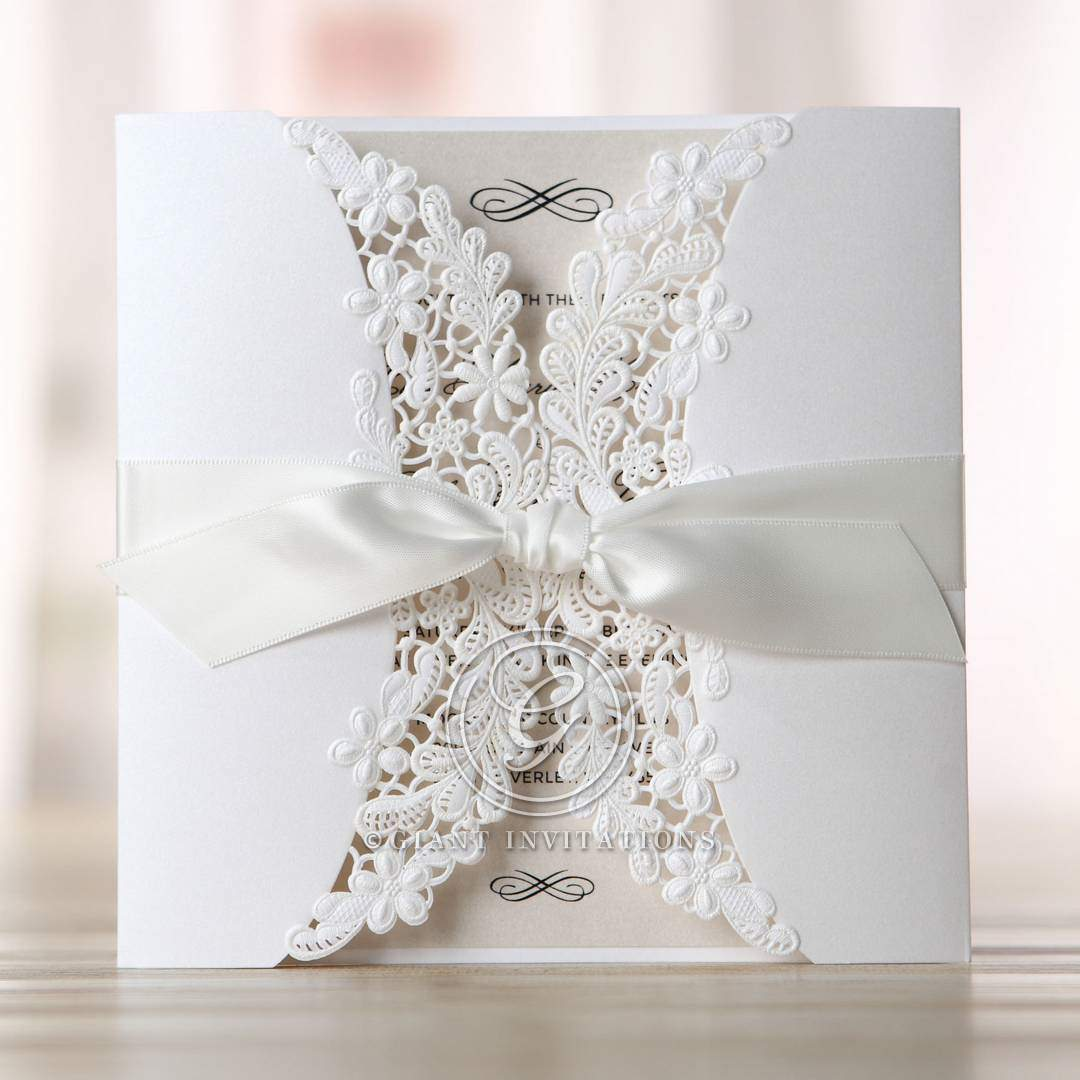 Intricate floral patterned lasercut details on a white gatefold invite, wrapped in a silky smooth satin ribbon