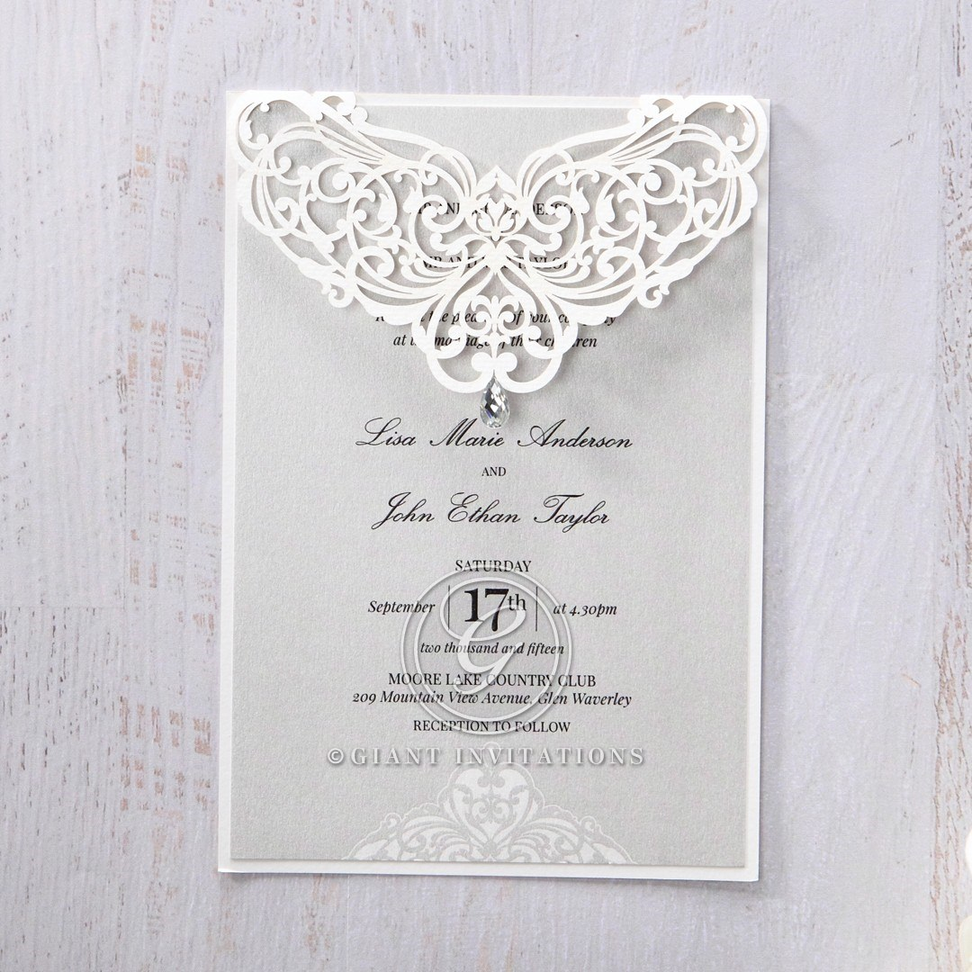 Shiny light grey pearlised insert paper on a matte white backing card with intricate lasercut flap adorned with crystal