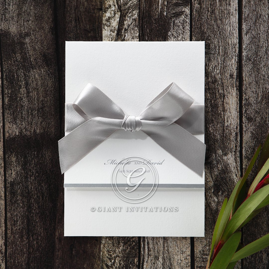 Lightly textured white invite bound by an elegant silver ribbon