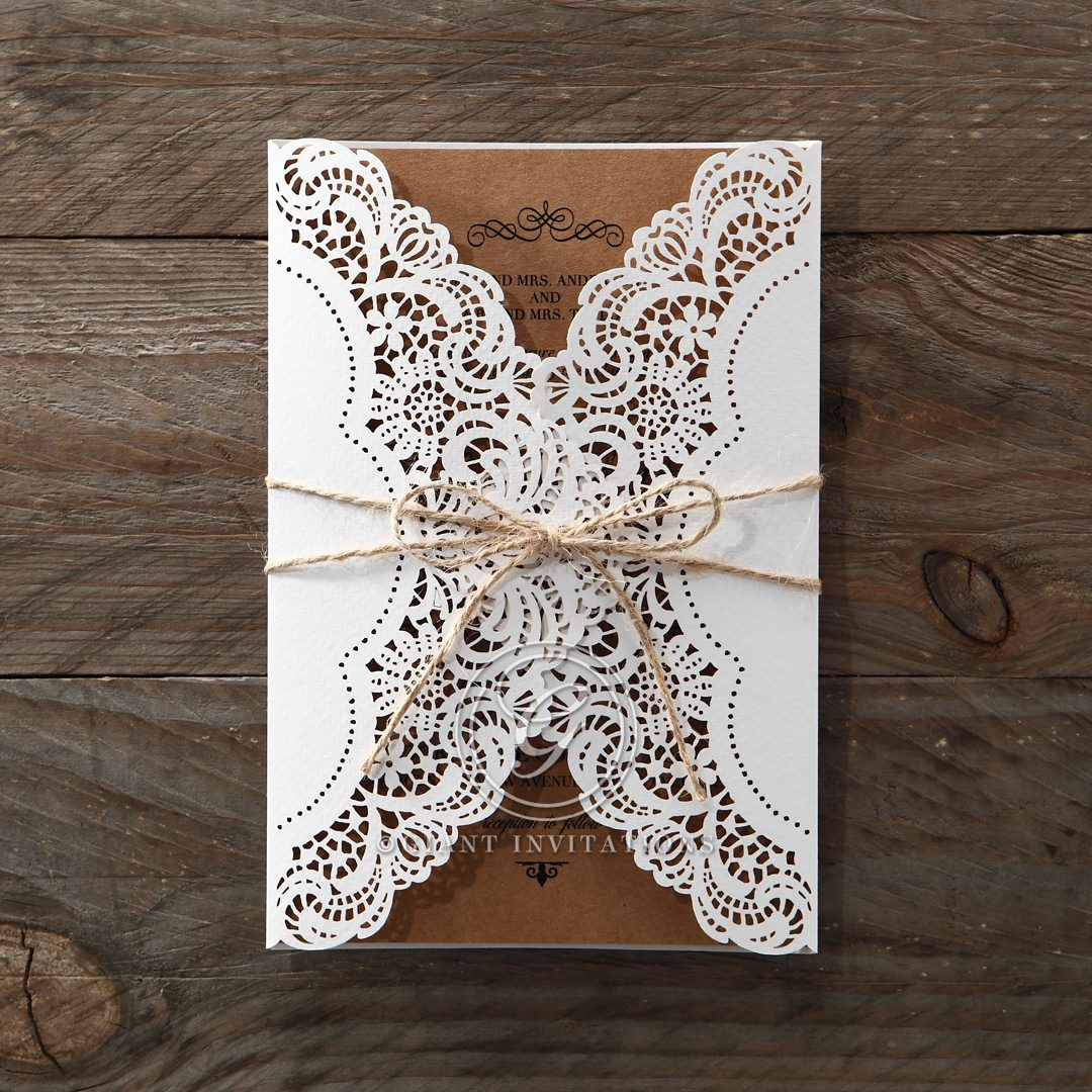 Intricate lasercut sleeve on a white pocket invite wrapped with twine, enclosing a brown craft card