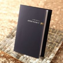 Dark blue booklet style announcement card with hand assembled jewel and foil stamped cover