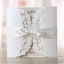 Traditionally style white laser cut pocket invitation featuring intricate floral patterns and satin ribbon in white; thermography printed