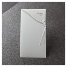 Simplistic white pocket with silk screened lining, ribbon and embossed text in front