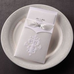 Textured trifold insert card in high rise fonts, enclosed in a delicately made pocket with embossed vintage theme detail, adorned with a silky-smooth ribbon with a jeweled center