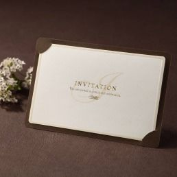 Deep brown backing layer enclosing an elegant ivory card with gold foiled lettering and round edged borders enclosed in a pearlised paper
