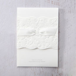 Stunning lightly textured insert paper in raised ink printing, attached to a gorgeous white pocket, with embossed floral details, adorned with a white bow