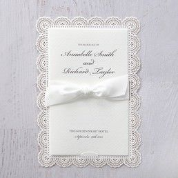 Luxurious textured ivory coloured card wrapped with a white satin bow, attached to a sturdy white coloured backing card with floral die cut borders
