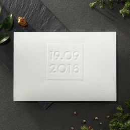 Minimalistic lightly textured card featuring an embossed date on outer cover and calligraphic wording on the main invite