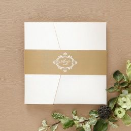 Unique pocket invite with white inner card adorned by majestic golden borders, enclosed in an ivory coloured pocket, bound by a golden paper band