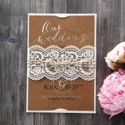 Rustic brown craft paper, gold foiled stamp in calligraphic letters enclosed in a matte white card with lace inspired sleeve wrapped with a twine