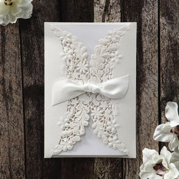 Bright white trifold card printed in calligraphic fonts inserted in a gorgeous gatefold pocket with laser cut flap adorned with a ribbon
