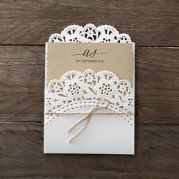 Dashing matte white pocket invite with floral die cut brim bound by a twine enclosing a brown craft paper printed in raised ink