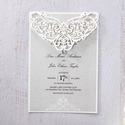 Shiny light grey inner card with raised printing, highlighting the wedding day in bold font, set in a white backing paper with a sophisticated laser cut design and jewel stud
