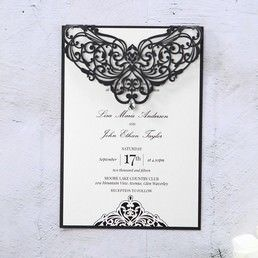 Black and white invite printed in raised ink, draped with an intricate laser cut flap, adorned with a jewel stud