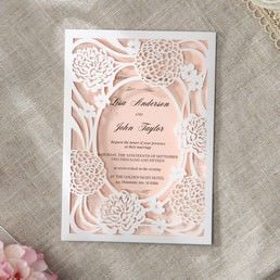 Charming light peach insert card printed in raised ink draped in a gorgeous floral laser cut pocket with oval center highlighting the details of the main invite