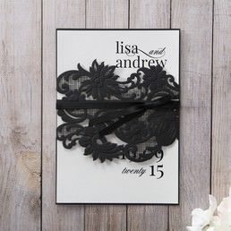 Elegant black coloured backing paper with embossed flower themed laser cut sleeve, enclosing a classic matte white insert card with calligraphic writing