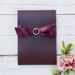 Classic matte white card with regal themed border enclosed in a stunning shimmering mulberry coloured pocket bound by a violaceous satin bow