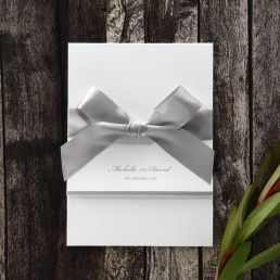 Sophisticated trifold card with pre-stamped silver foiled letters, enclosing an embossed insert card wrapped with a sparkling silver ribbon