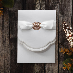 Dazzling golden emblem atop the main invite surrounded by a golden border, enclosed in a lightly textured pocket with front envelope, adorned by a satin ribbon