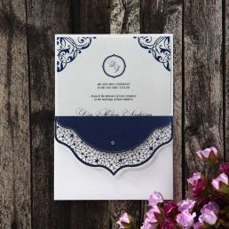 Pearlised white card with deep blue vintage themed borders inserted in a pocket invite with built in mini envelope in laser cut details adorned with a sparkling crystal