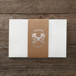 Lightly textured trifold card with wooden themed embossed pattern bound by a brown organic paper with silver foiled crisscross key symbol