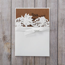 Dashing white invite with embossed floral die cut details bound by a dainty ribbon, enclosing an organic brown card printed in raised ink