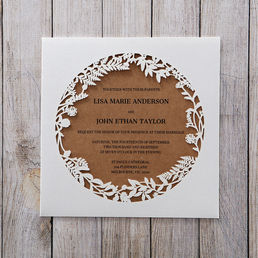 Organic brown card printed in high rise fonts inserted in a pocket with circular cut out center, embellished with die cut leaf inspired brim