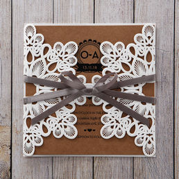 Embossed floral die cut gatefold sleeve adorned with a light grey silky ribbon, enclosing an organic brown card printed in raised ink