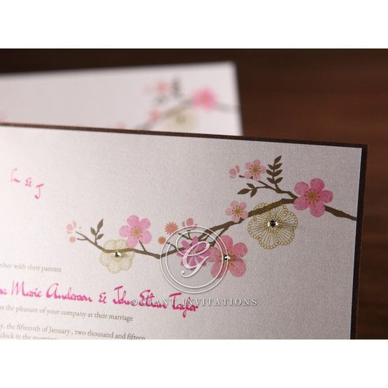 Pink floral designed invitation accented with jewels and chocolate brown trim, closeup