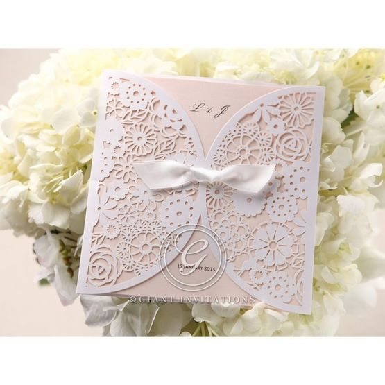 Ribboned laser cut white floral invitation; pink inner paper