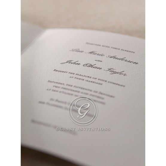 Zoomed in view of the black raised ink on matte white invitation with embossed frame