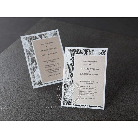White laser cut bordered card with peacock design and cream colored invitation