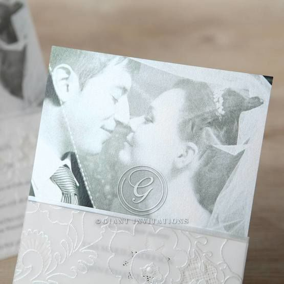 Zoomed in photo detail of the traditional white photo invite, folded accented with embossed and silkscreened designs