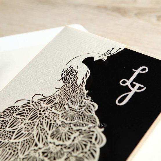 Close up view of white laser diet cut pocket feature a peacock design with digital printed monogram in black and white