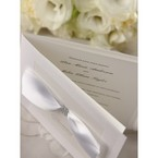 Pure white wedding invitations with ribbon and jewel, top views