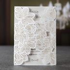 White gatefold invite with laser cut lotus flower design enclosing a pearlised inner card