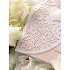 white floral laser cut details on light pink wedding invitation