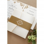 White lightly textured pocket invite wrapped around with a belly band with golden shimmer, and white monogram center