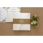 A shiny golden belly band with white monogram, and an opened pocket invite with matching stationeries