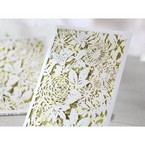 Opened white laser cut wedding invitation, beige inner paper