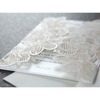 Intricate laser cut sleeve enclosing a pearl card with black ink writing