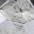 Cropped, unfolded flap of white lasercut peacock wedding invitation